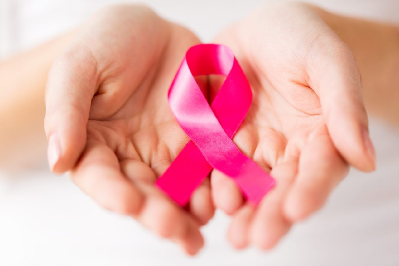 healthcare, charity, people and medicine concept - close up of woman cupped hands holding pink cancer awareness ribbon