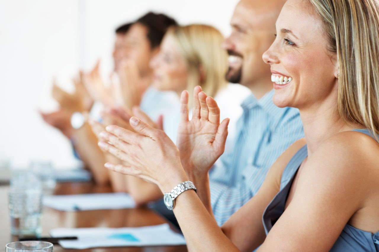 Pretty young business woman with colleagues applauding at a seminar - Congratulations